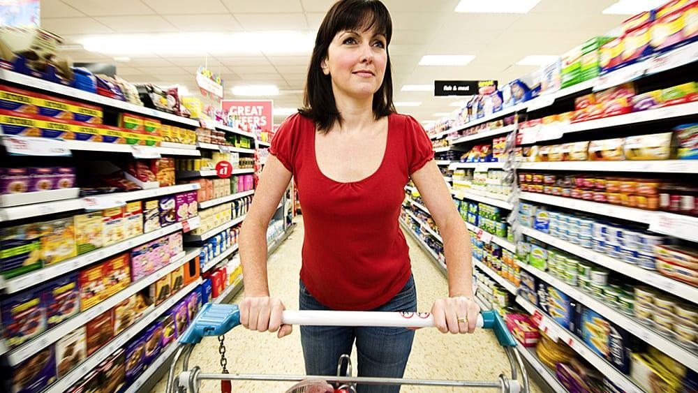 Девушка в магазине с множеством товаров и привлекательными этикетками и упаковкой